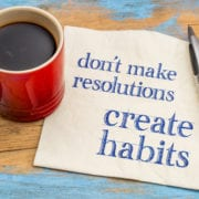 Do not make resolutions, create habits  - motivational advice or reminder on a napkin with a cup of coffee
